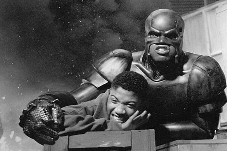 Still from the movie Steel of Shaquille O'Neal in his Steel armor saving a boy, with an explosion in the background