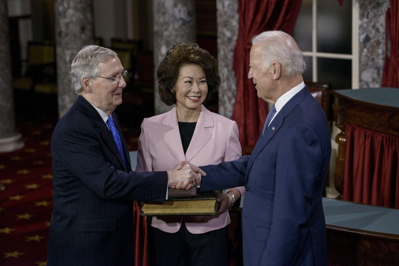 McConnell and Biden shake hands while Elaine Chao smiles in the background
