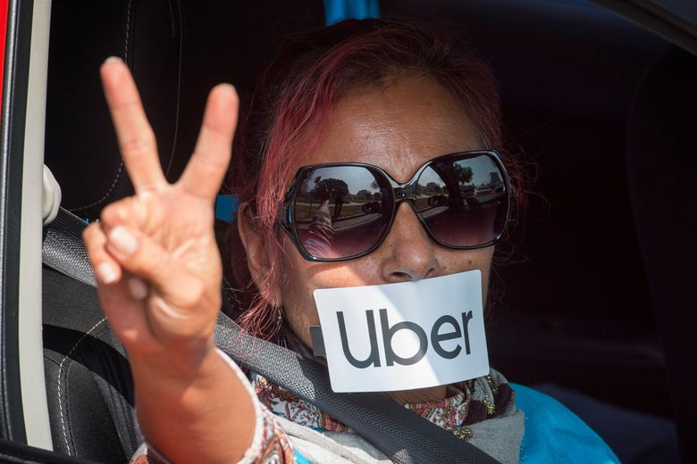 A woman sitting in a car making a peace sign with her hands with an Uber sticker on her mouth