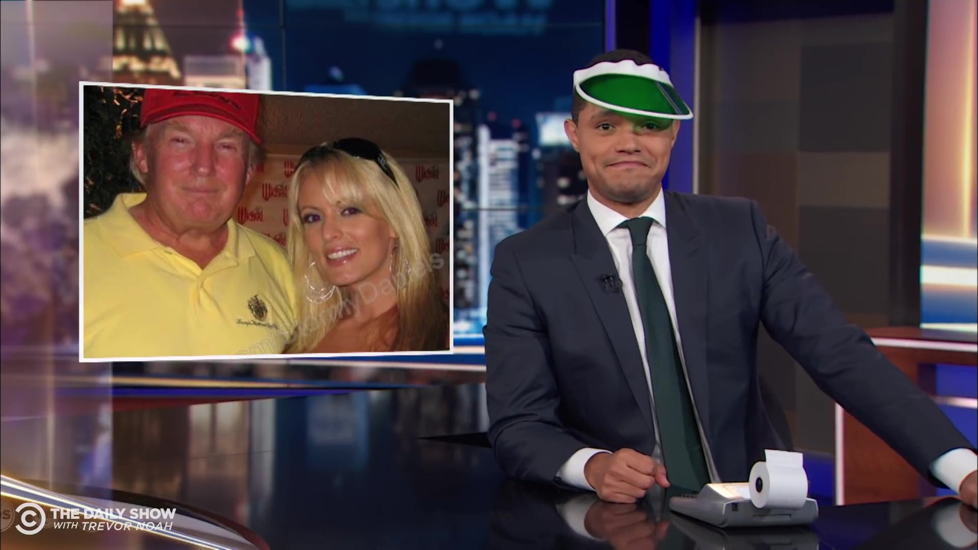 Trevor Noah, wearing an accountant's green eyeshade, in front of a picture of Trump and Stormy Daniels.