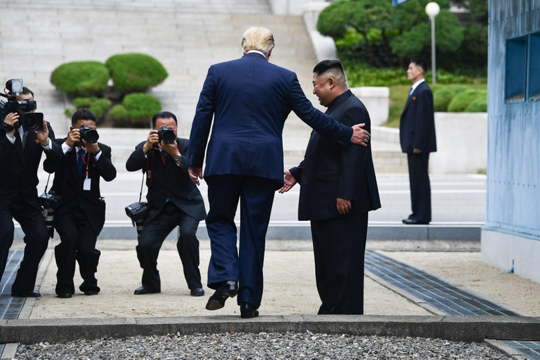 Trump walks across the border as Kim looks on.