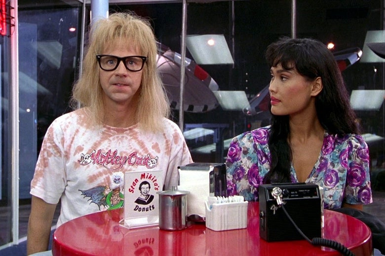 "Dana Carvey, wearing thick, black-framed glasses, sits with Tia Carrere at a table. A small sign reads ""Stan Mikita's Donuts."""