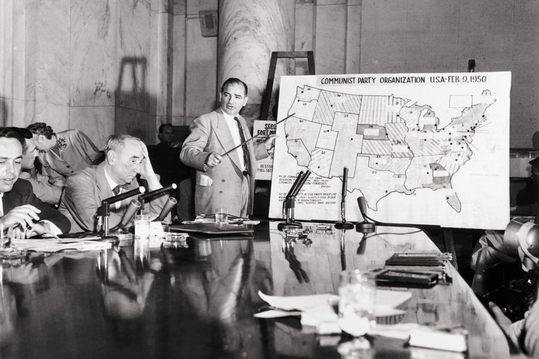 Sen. Joseph McCarthy points to a map depicting Communist Party organization across the U.S., in front of a conference table where Army counsel Joseph Welch and others are seated. Welch holds his head with his left hand in frustration.