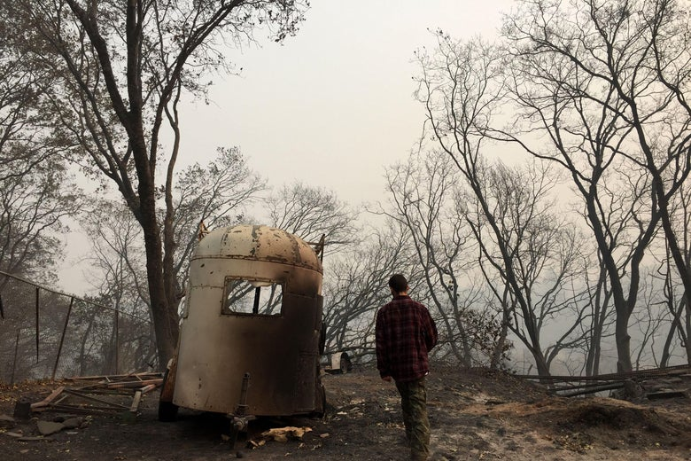 A man in Paradise, California, walking into the burned-out remnants of his home