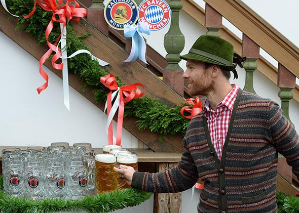 Bayern Munich's midfielder Xabi Alonso grabs a Paulaner on arrival for the traditional visit of the football club to the Oktoberfest beer festival on the Theresienwiese in Munich, on Oct. 5, 2014