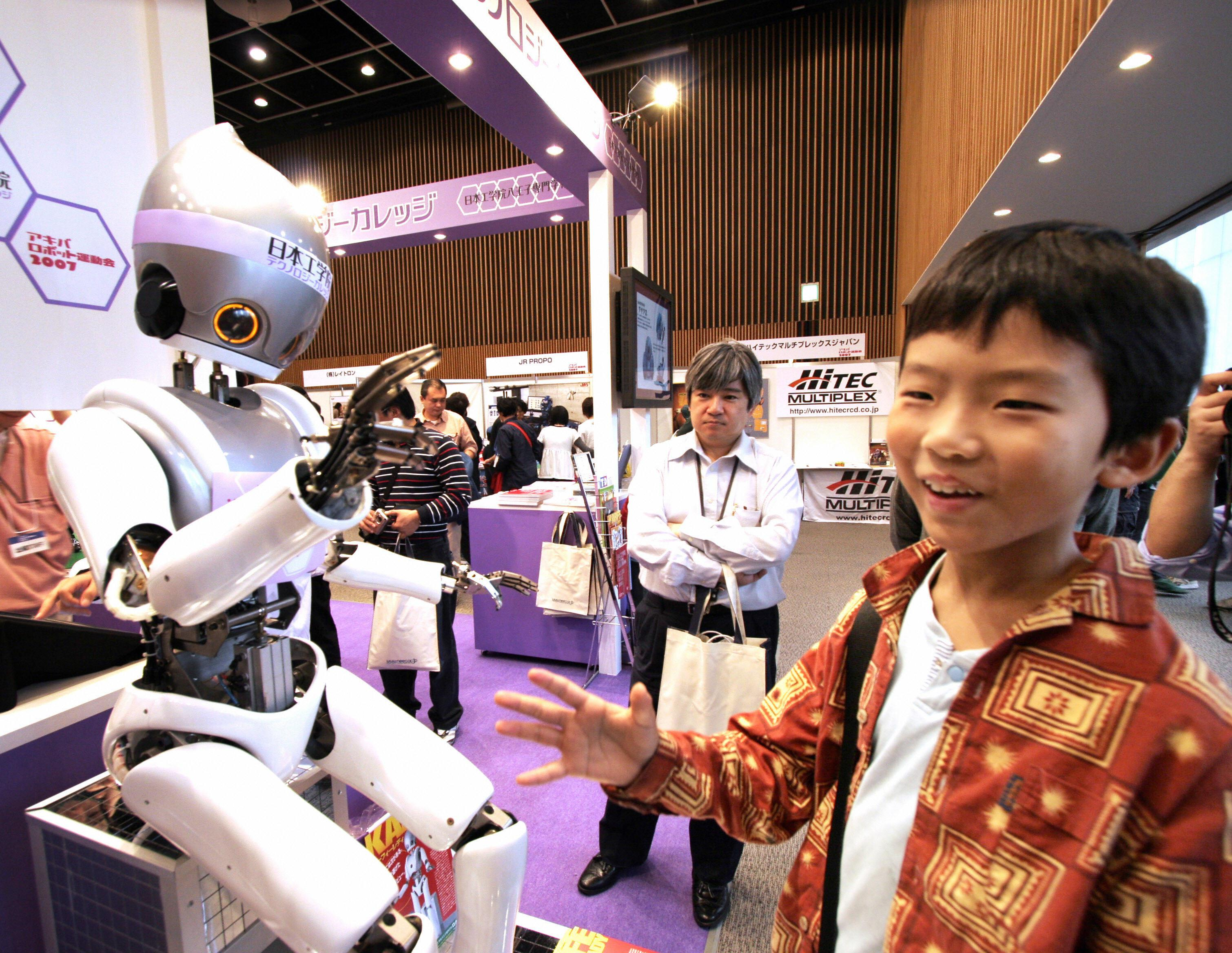 A boy plays rock paper scissors with a humanoid robot in Tokyo.