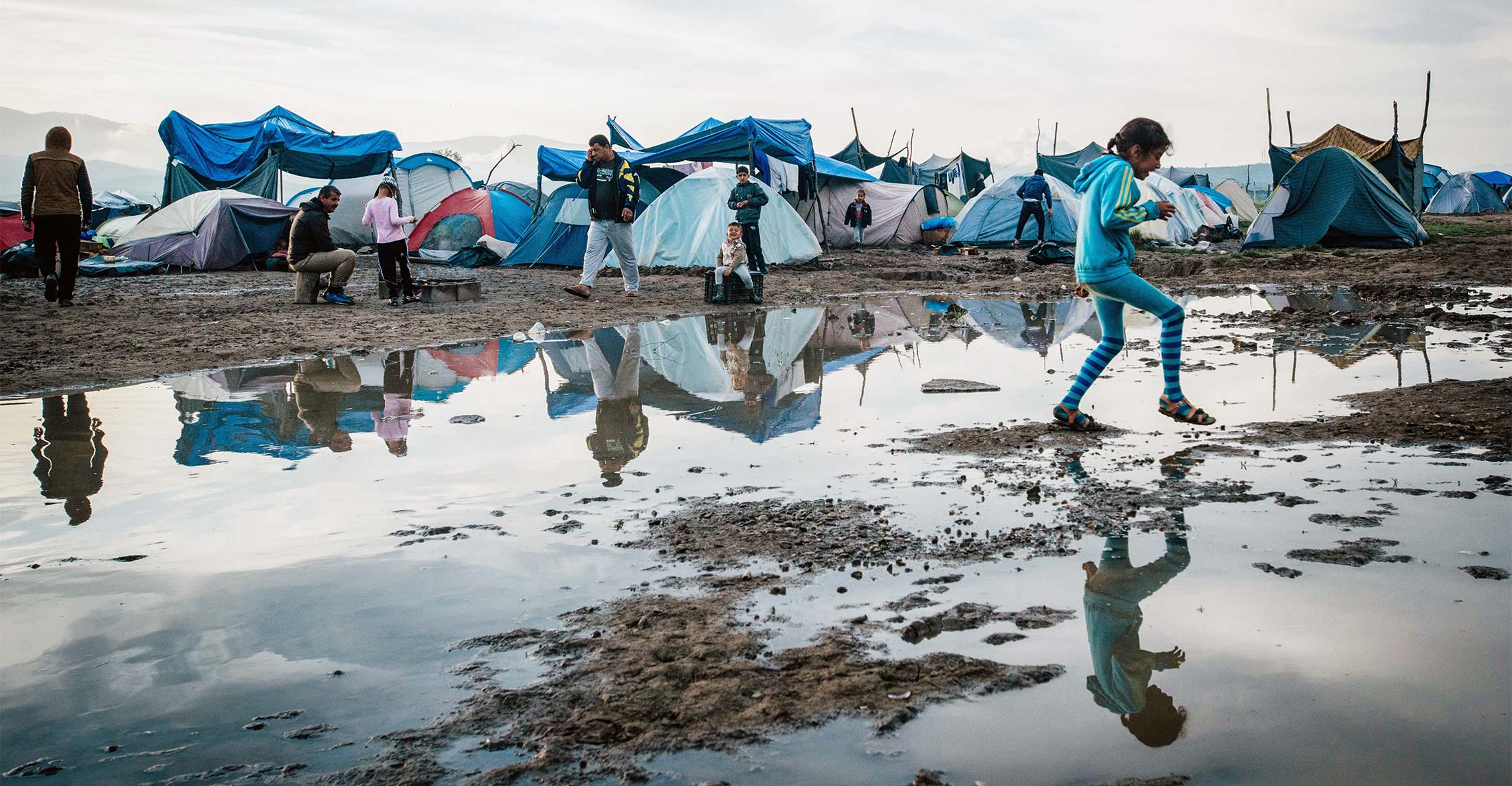 A refugee child jumps through puddles in front of makeshift tents.