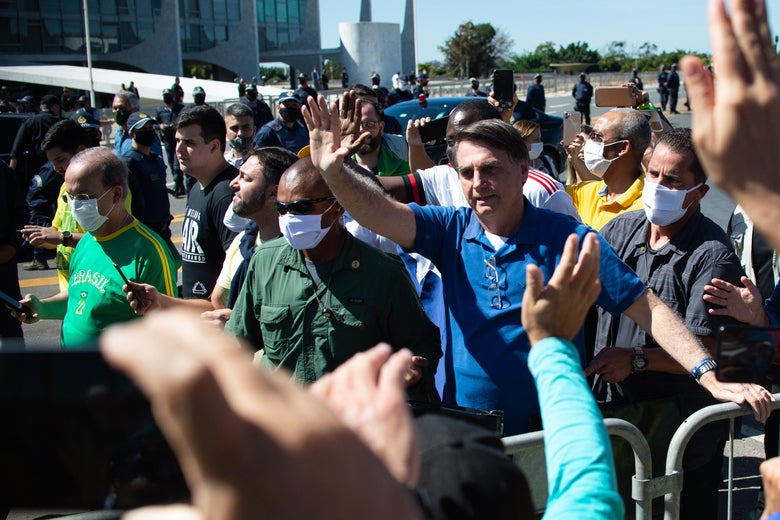 A maskless Bolsonaro waves to a crowd.
