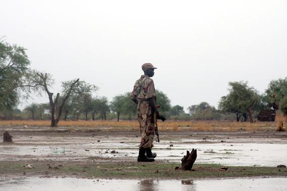 A soldier of the southern government's Sudan People's Liberation Army stands guard in front of an area of Turalei that is now home to thousands of displaced people from Abyei.