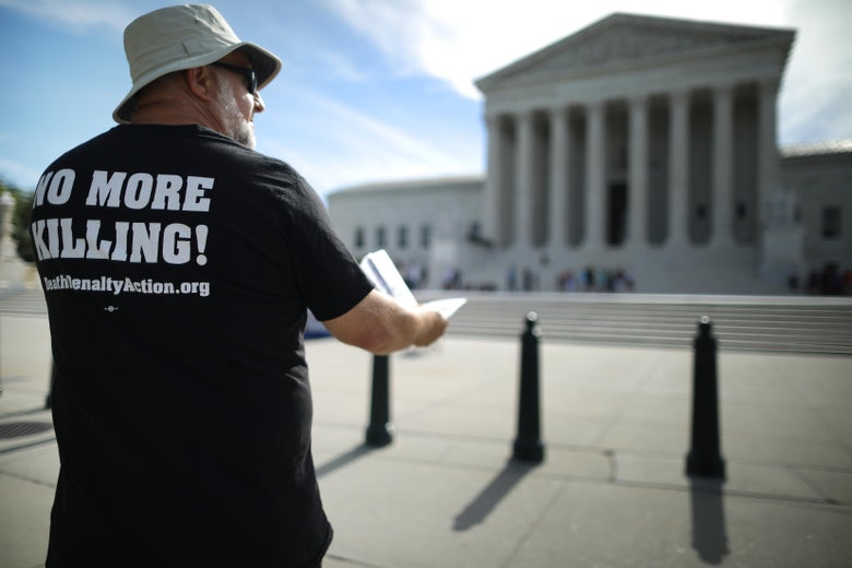 """A death penalty abolitionist wearing a T-shirt that says """"NO MORE KILLING"""" protests in front of the Supreme Court"""