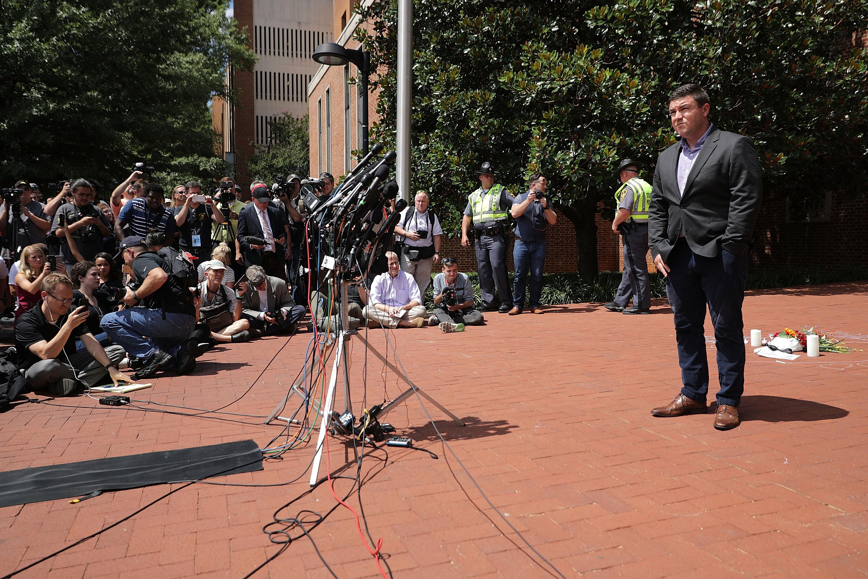 Jason Kessler stands in front of a crowd at a news conference.