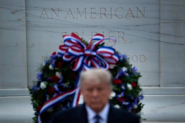 Donald Trump in front of a monument with a wreath laid on it.