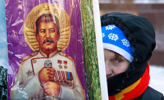 A woman holds a poster illustrating the late Soviet leader Josef Stalin before a ceremony to mark the 60th anniversary of his death in Red Square in central Moscow March 5, 2013.