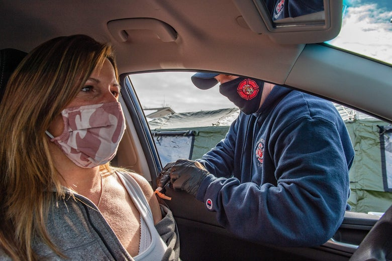 A first responder vaccinates a woman through the window of her car.