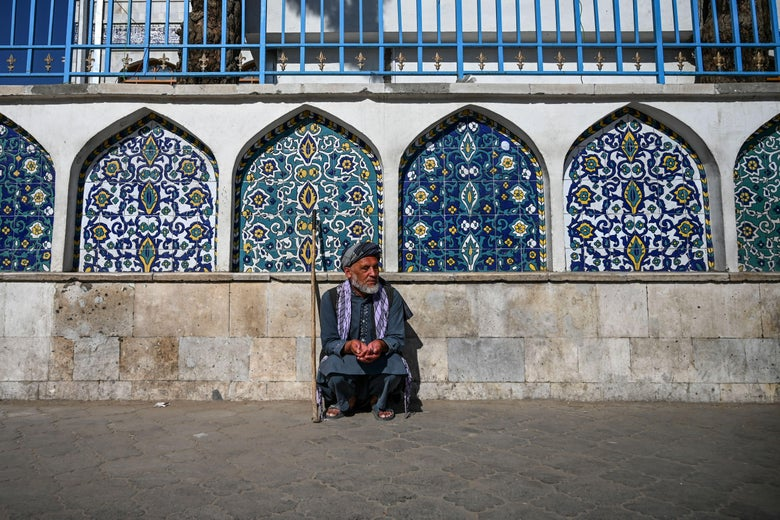A man squats in front of ornate windows on the exterior of the mosque