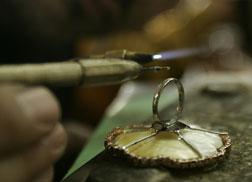 A goldsmith works on a gold ring. Click image to expand.