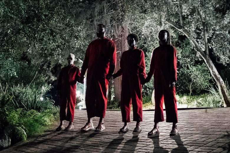 Four people wearing red jumpsuits hold hands while on top of a roof, in the film Us.