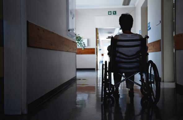 Person in a wheelchair in a darkened hospital corridor.