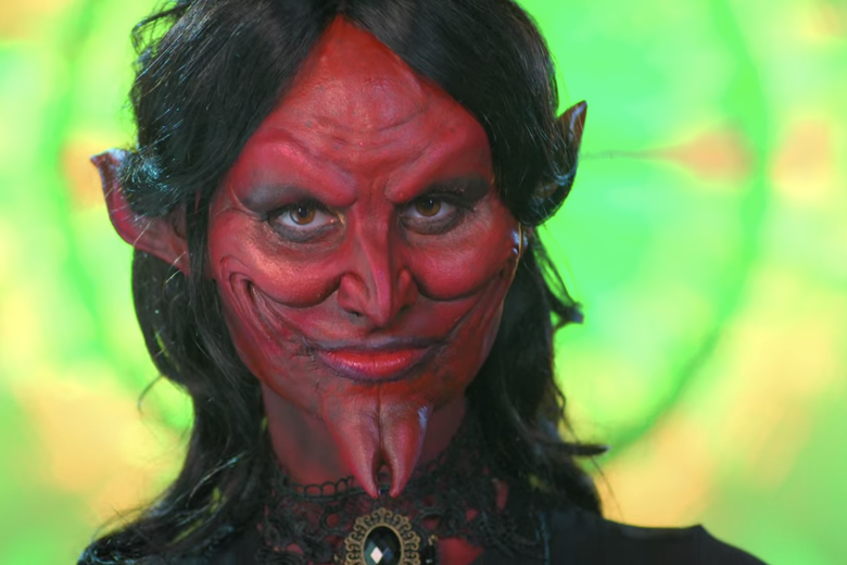 Woman wearing a pointed red devil mask.