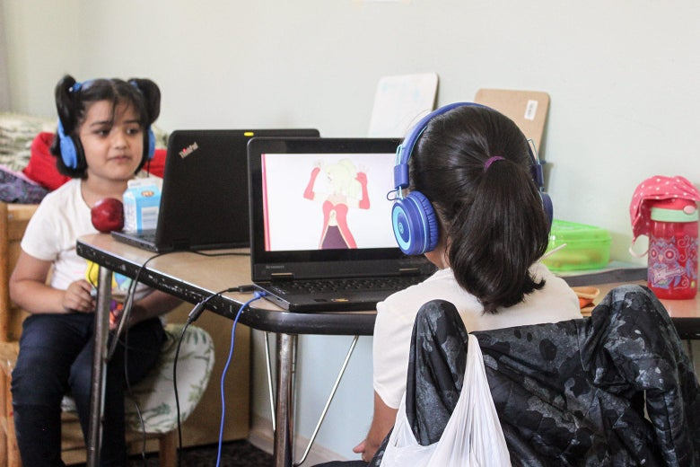 Two small children in large blue headphones sit behind laptops.