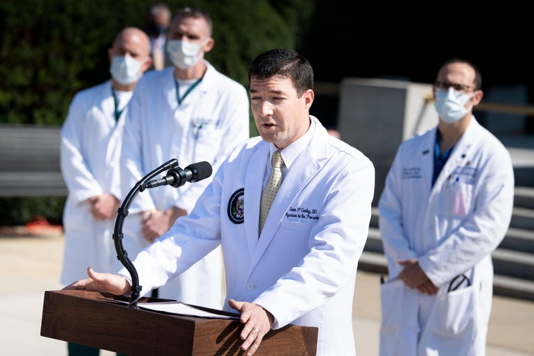 Sean Conley speaks at a lectern. Other doctors wearing masks are seen in the background.
