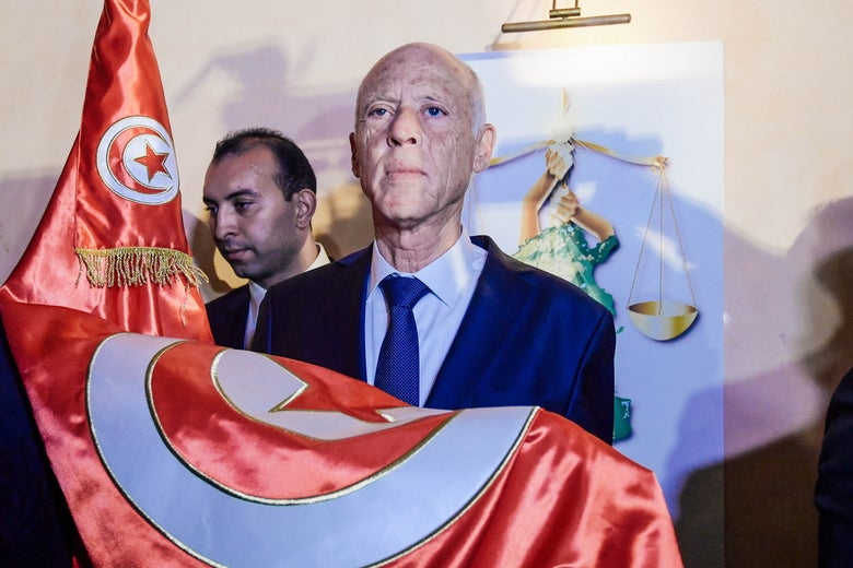 Kais Saied holds the Tunisian flag in his hands.