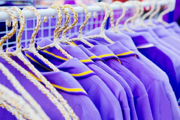 A series of purple shirts hanging on a rack