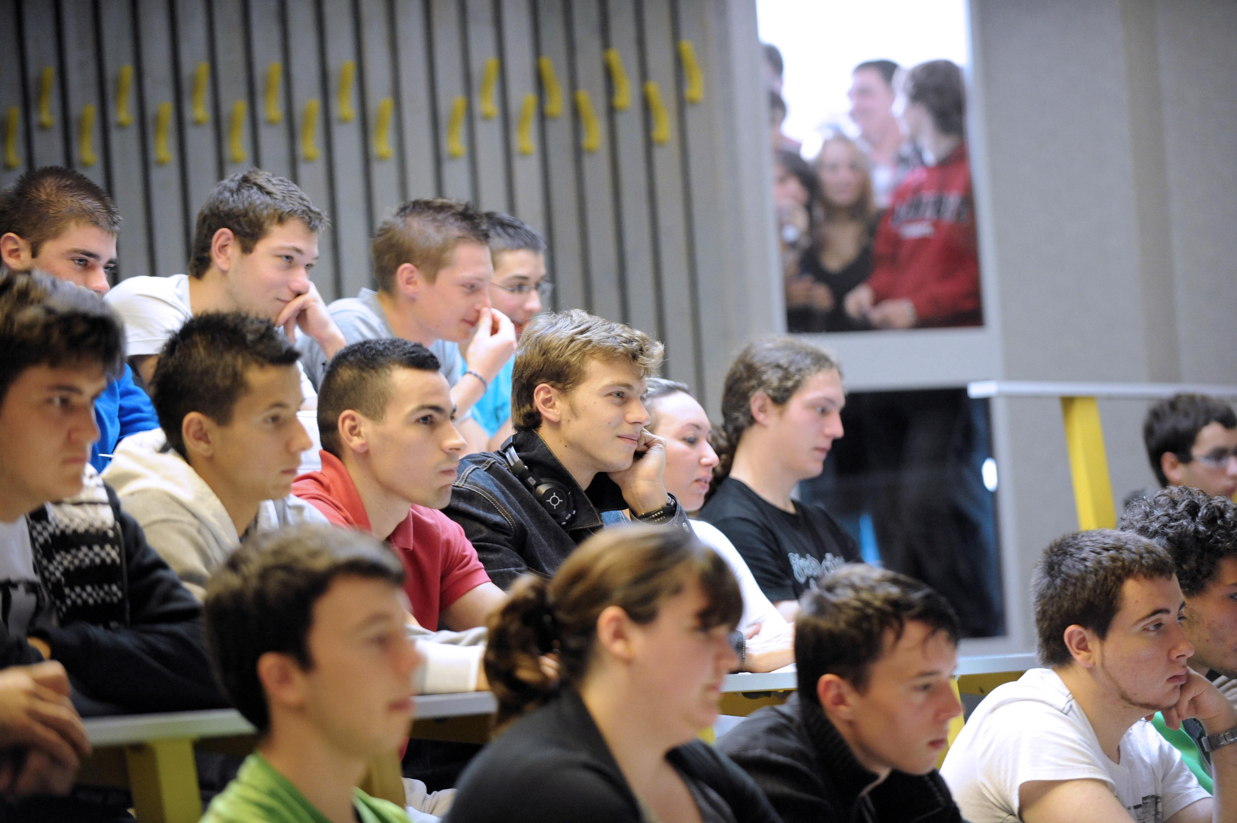 A group of freshmen economy students stand together chatting after they attended an information lecture 16 October 2003 in an auditorium of the technical university of Berlin at the beginning of the winter semester.
