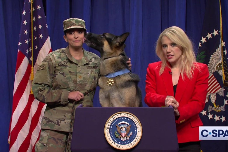 Kate McKinnon dressed as Kellyanne Conway, Cecily Strong in an Army uniform, and a German Shepherd stand behind the White House briefing room podium in a still from SNL.