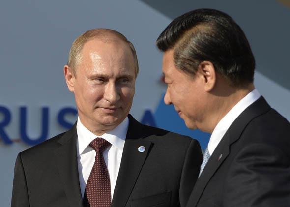 Russia's President Vladimir Putin (L) welcomes China's President Xi Jinping at the start of the G20 summit on September 5, 2013 in Saint Petersburg.