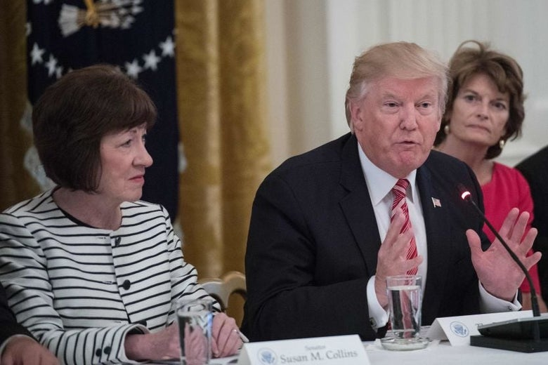 Collins and Murkowski flank Trump, who raising his hands and speaking into a microphone. All three are seated at a table.