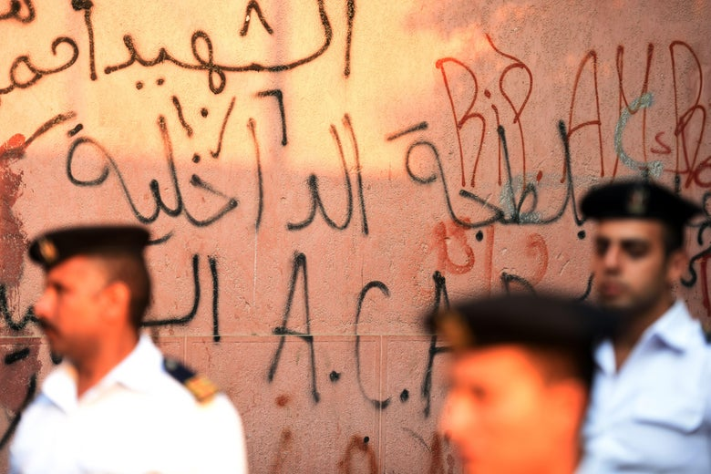 Egyptian police officers stand before a wall covered in graffiti.