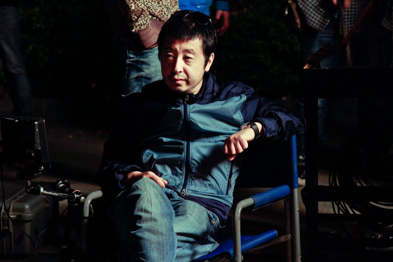 Director Jia Zhangke sitting in a director's chair.