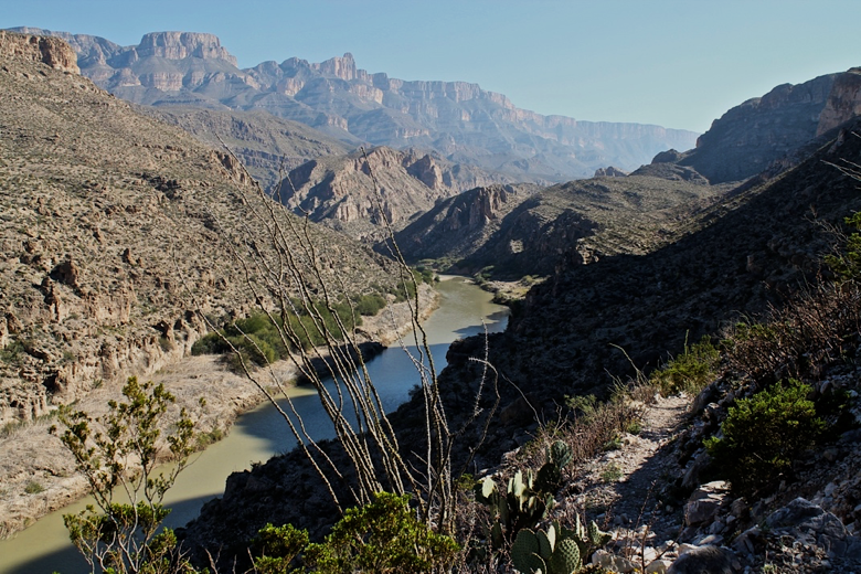 A muddy river surrounded by mountains and desert scrub.