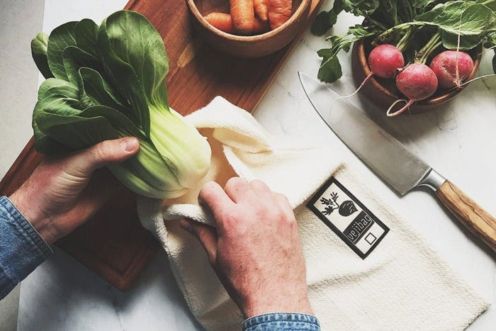 Hands putting a vegetable into a produce bag.