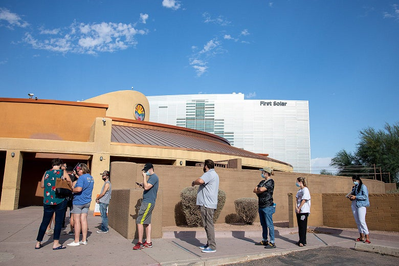Voters wait in a spaced-out line outside a theater on a sunny day.