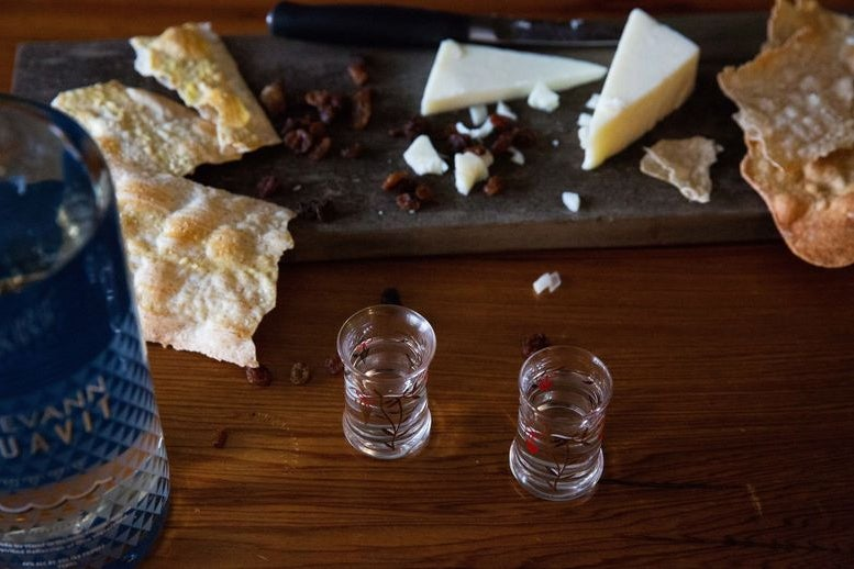 Two tiny glasses next to a bottle of aquavit and a plate of cheese and crackers on a table