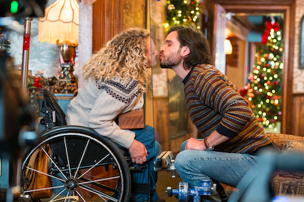 Actress Ali Stroker and her costar Daniel di Tomasso kiss the plexiglass between them. Christmas decorations light up the room behind the two of them.