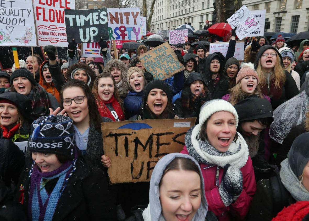 """Protesters march, chant, and hold up signs with feminist slogans such as """"Time's Up"""" and """"Women's Rights Are Human Rights."""""""