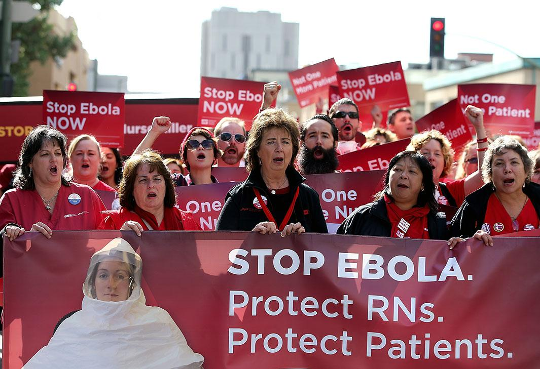 Nurses hold signs as they march to a demonstration outside of the Dellums Federal Building on November 12, 2014 in Oakland, California.