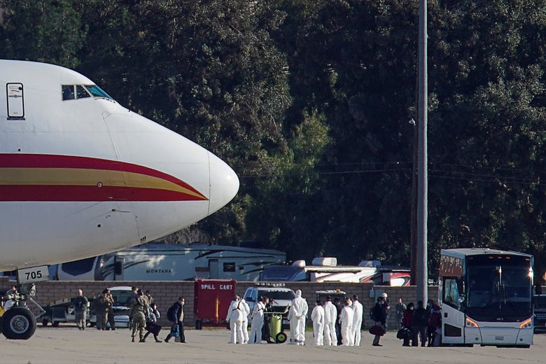Passengers walk away from a jet and towards a bus. A group of officials in white protective clothes stand between the jet and the bus.