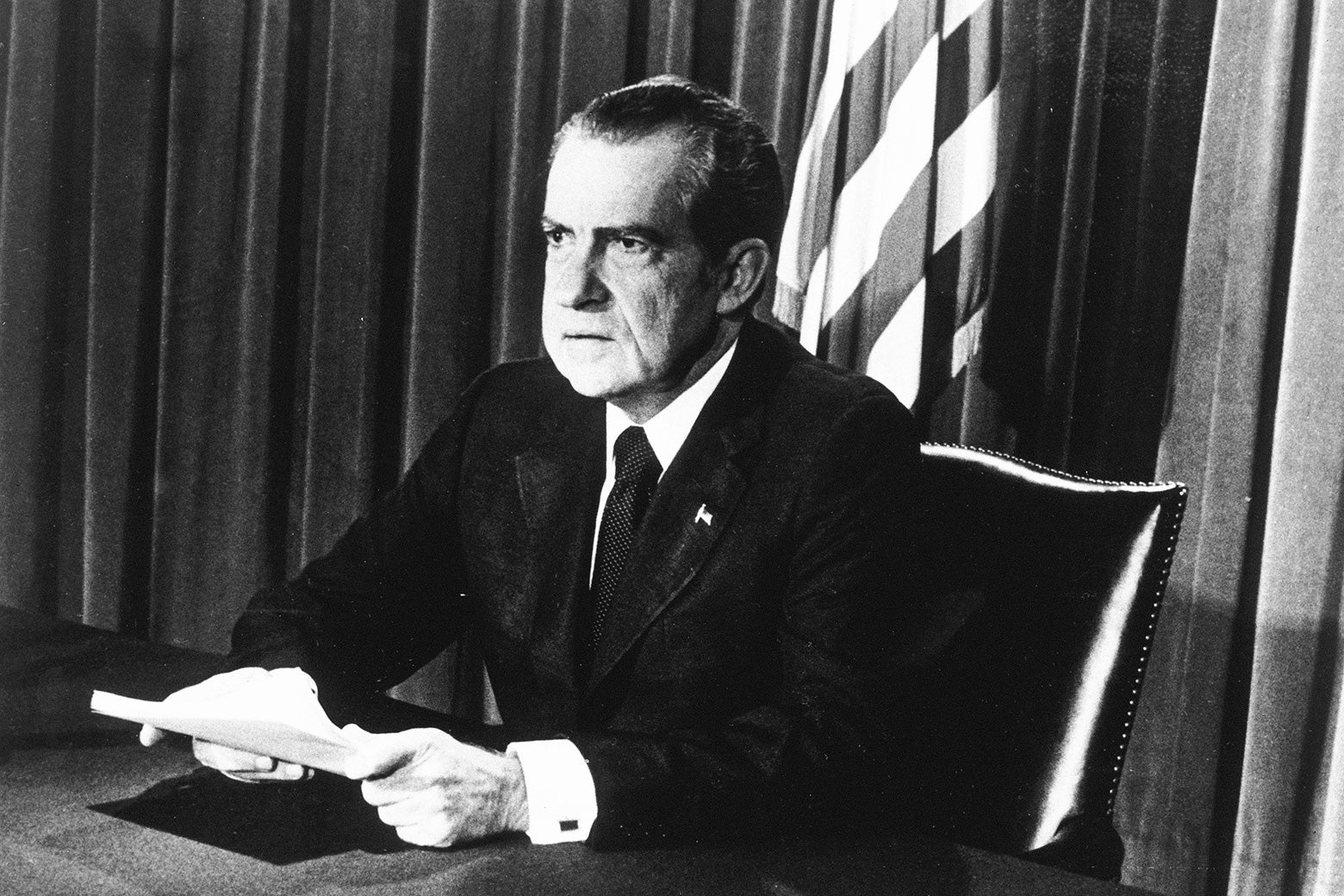 U.S. President Richard M. Nixon sits at a desk, holding papers, as he announces his resignation on television, Washington, D.C.