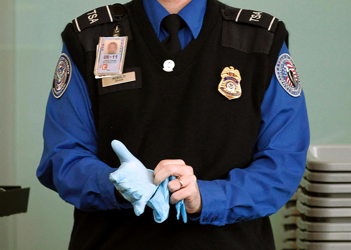 A TSA agent dons rubber gloves at a security checkpoint at Washi,A TSA agent dons rubber gloves at a security checkpoint at Washington.