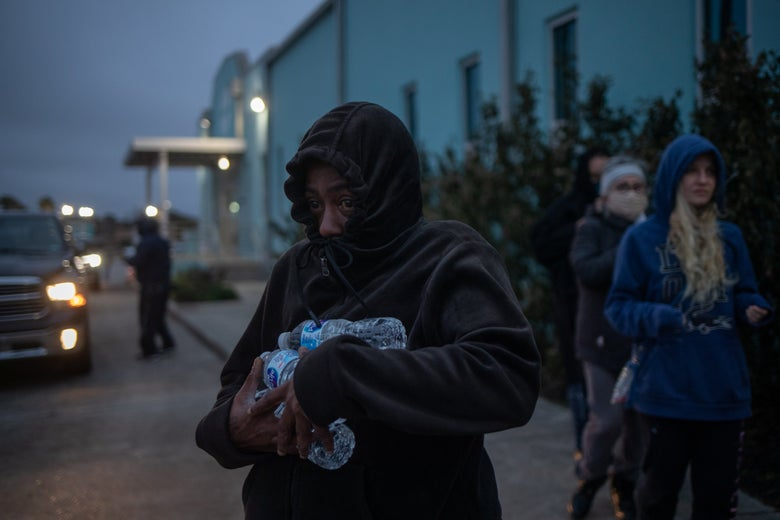 Woman bundled up carrying a few bottles of water