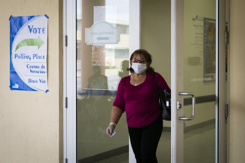 "A woman wearing a surgical mask and gloves exits the polling place. A ""VOTE"" sign hangs on the wall next to the doors."