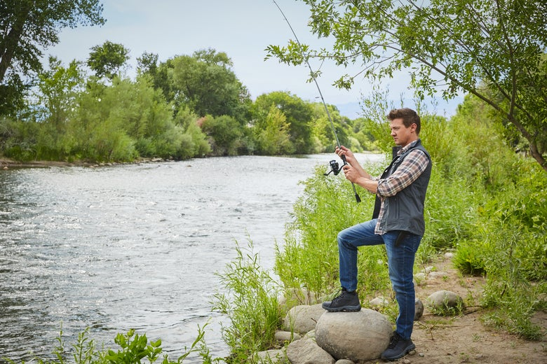 Jeremy Renner stands with one foot on a rock, holding a fishing rod that appears to have no line cast.