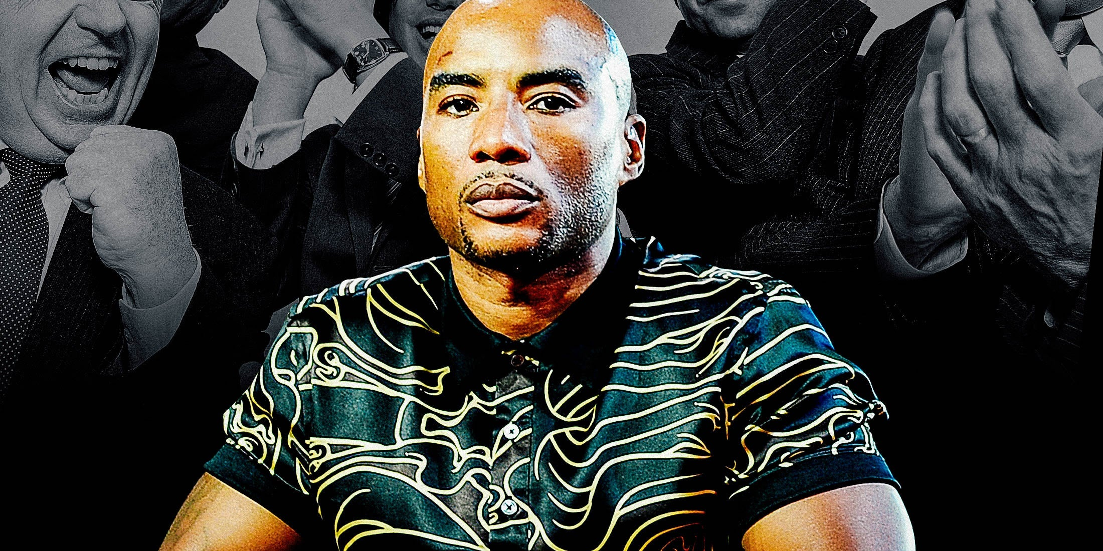 Charlamagne tha God seated, with white people in suits standing and cheering in the background