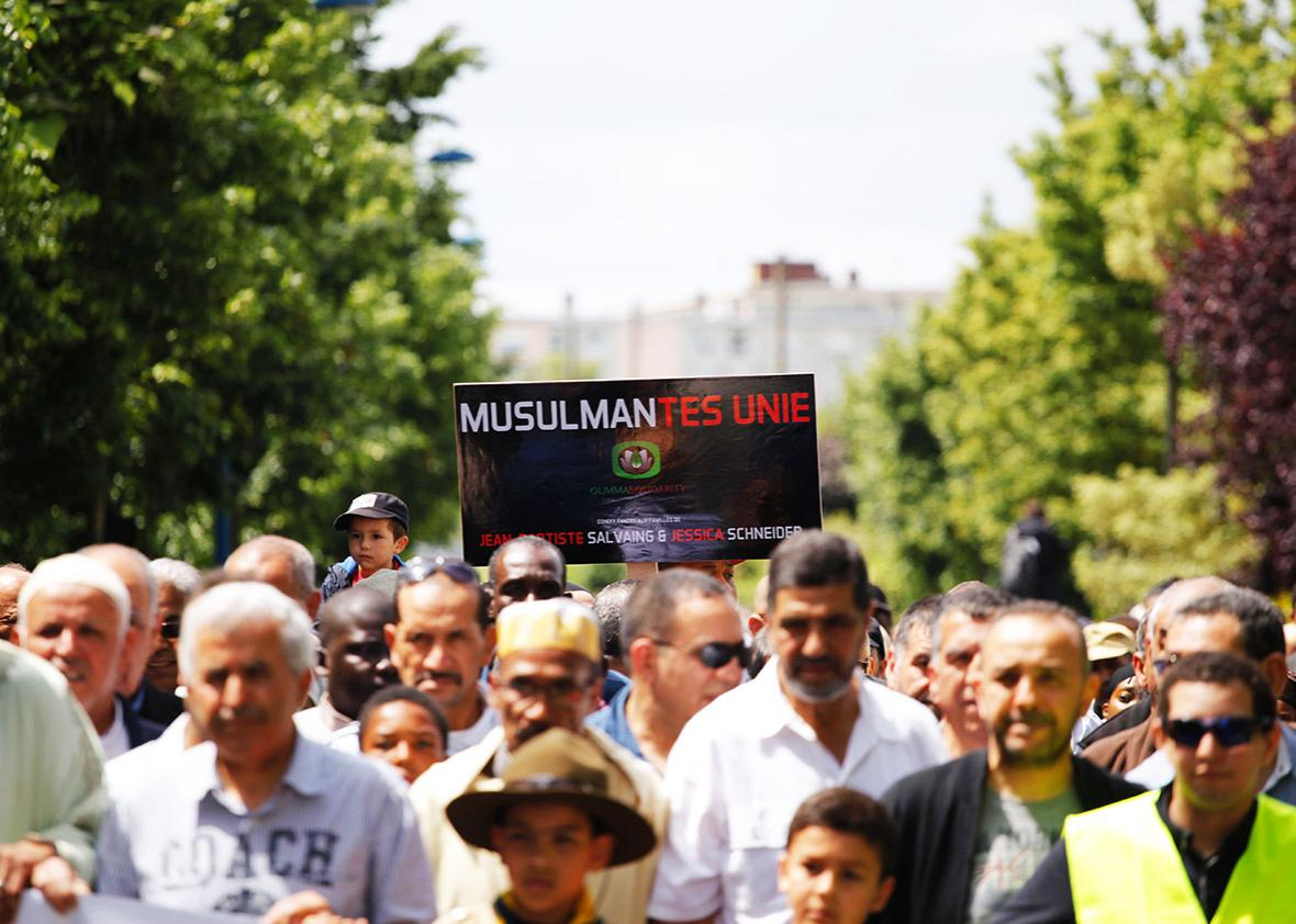 """A participant holds up a placard reading """"Muslims-Mantes United"""" as people take part on June 19, 2016 in Mantes-la-Jolie in a silent march in memory of the French police officer and his partner stabbed to death on June 13 by a convicted extremist who had pledged allegiance to the Islamic State group."""