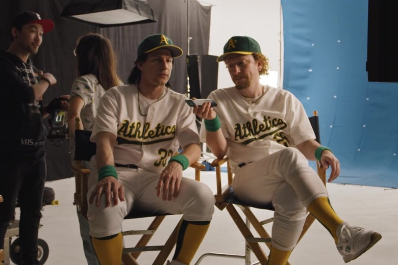 Andy Samberg and Akiva Schaffer, in Oakland A's uniforms, sitting on director's chairs and looking at a drum.