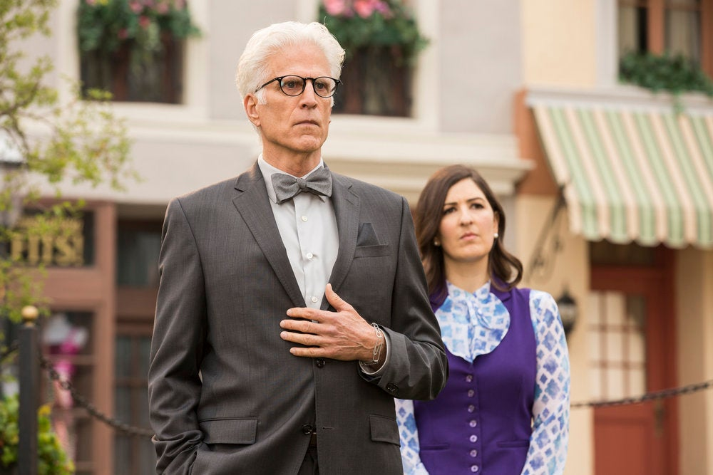 Ted Danson stands with his hand on his chest. In the background, D'Arcy Corden looks on.